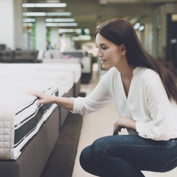 A woman in a white shirt and jeans in a mattress store. She examines the mattress she wants to buy. She squats and looks at the mattress